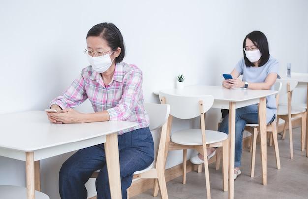 フェイスマスクを着用し、ビデオ通話、オンライン学習、または作業にスマートフォンを使用している2人のアジア女性が、安全な社会的距離を確保するために別々のテーブルに座っています。
