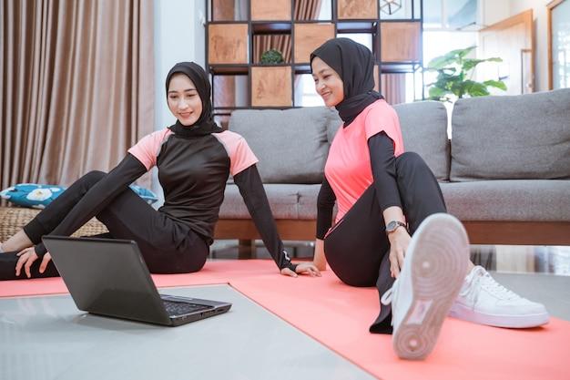 ヒジャーブのスポーツウェアを着た2人のアジア人女性が、家の中で一緒に腰を温めながら床に座ります。
