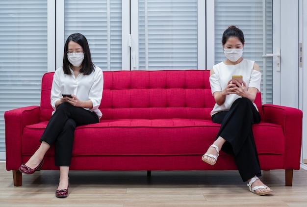 Two asian women wearing masks working at home or work remotely using smartphone to reduce spreading of coronavirus infection during covid-19 outbreak.