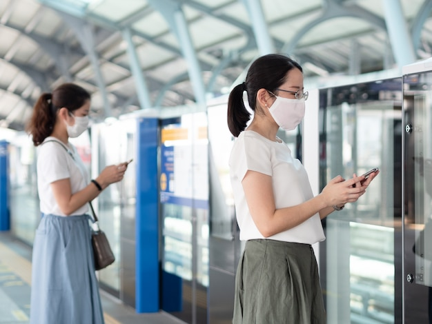 Two asian women wearing medical face mask, using smartphone waiting for metro at train station platform, standing distance apart from other people.