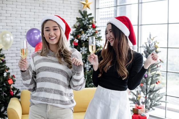Две азиатские женщины с напитками и танцами в рождество