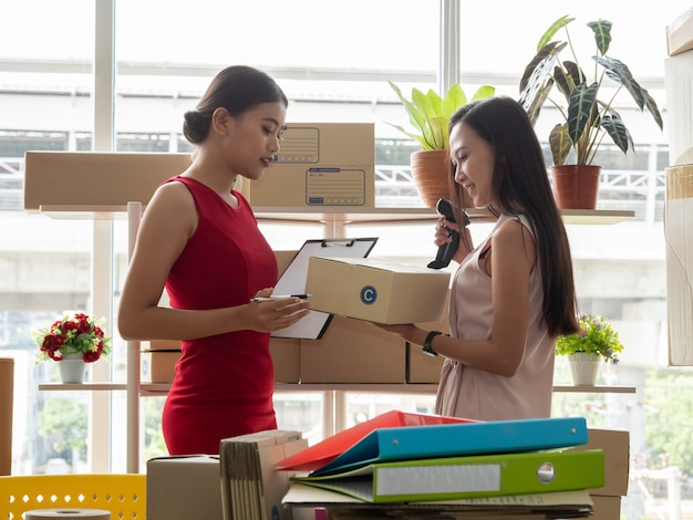 Two asian women with startup small business entrepreneur freelance working at home. checking product order.
