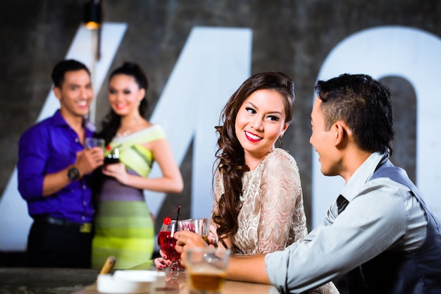 두 아시아 젊고 잘 생긴 파티 사람들이 고급스럽고 멋진 나이트 클럽의 바에서 유혹하고 술을 마시고 있습니다.