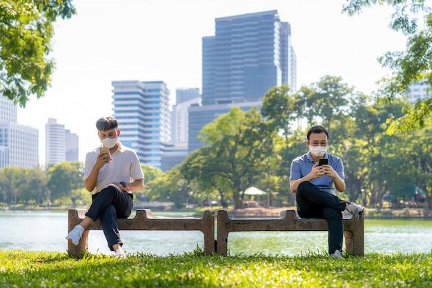 스마트 폰에서 채팅하고 6 피트 거리의 마스크 앉아 거리를 착용하는 두 명의 아시아 젊은이가 공원에서 감염 위험에 대한 사회적 거리를두고 covid-19 바이러스로부터 보호합니다.
