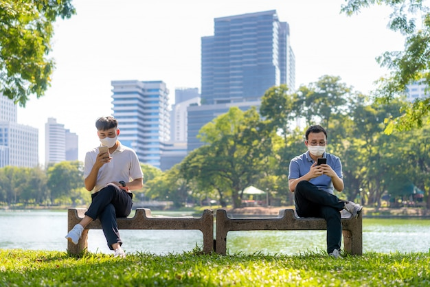Two asian young man chatting in smartphone and wearing mask sitting distance of 6 feet distance protect from covid-19 viruses for social distancing for infection risk at park