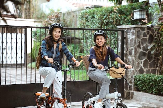 ヘルメットとバッグの準備ができて身に着けている2つのアジアの若い女性はキャンパスに行く
