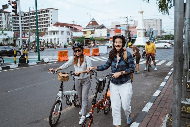 ヘルメットとバッグを身に着けている2つのアジアの若い女性は折りたたみ自転車で歩く