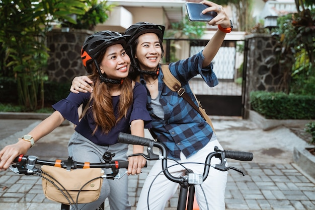 Two asian young woman wearing helmet and bags with camera cellphone make a video content on folding bike