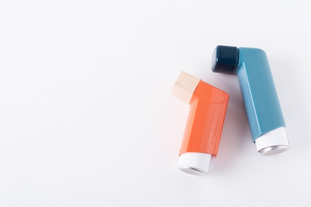Two asthma inhalers on an isolated on white . selective focus.