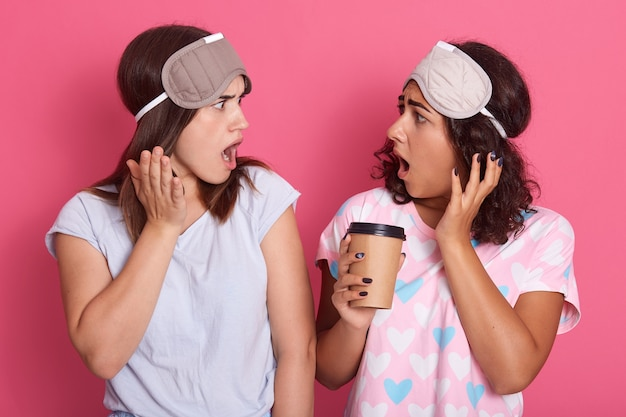 Two astonished dark haired females with widely opened mouths