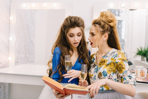 Two astonished pretty women looking at book in beauty salon
