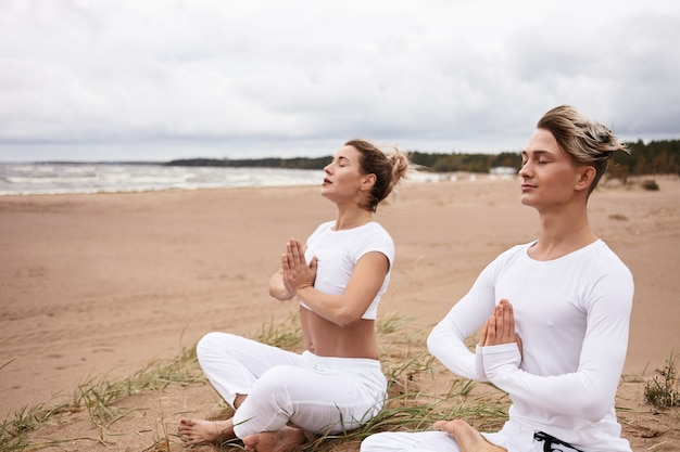 Due persone europee atletiche uomo e donna in abiti sportivi bianchi chiudono gli occhi e si tengono per mano in gesto di namste, seduti in padmasana mentre meditano all'aperto durante il ritiro di yoga in riva all'oceano