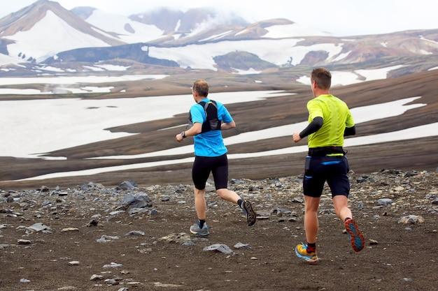 Two athlete runners run a mountain marathon in the snowy terrain of landmannalaugar