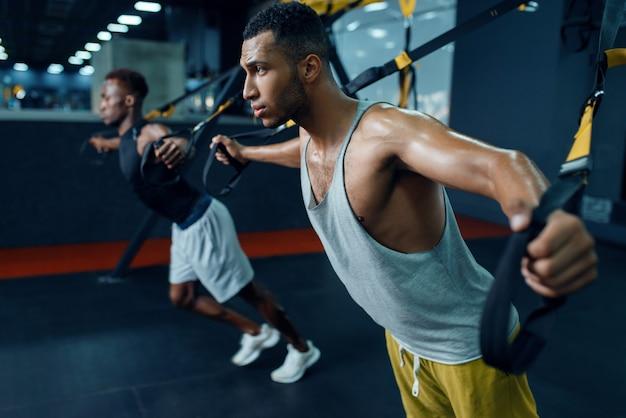 Два спортсмена на тренажере на растяжку