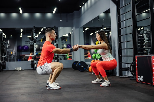 Two athletes, a beautiful woman and a handsome man are in a squatting position in the gym or fitness center