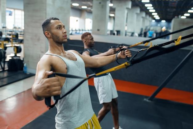 Два спортсмена в спортивной одежде на тренажере на тренировке в тренажерном зале