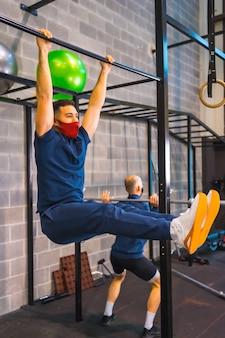 코로나 바이러스 전염병에서 체육관에서 근력 운동을 수행하는 두 선수