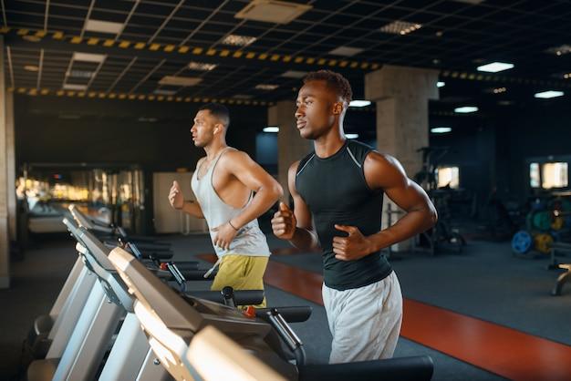 Два спортсмена бегут на беговой дорожке, тренируются в тренажерном зале