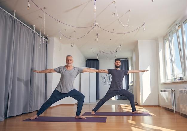 체육관에서 운동하는 동안 매트에 맨발로 서있는 두 운동 백인 남자