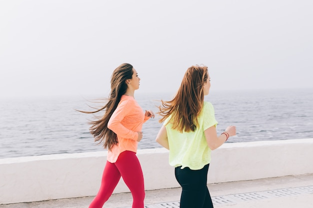 Two athletic girls with long hair run along the beach in sportswear