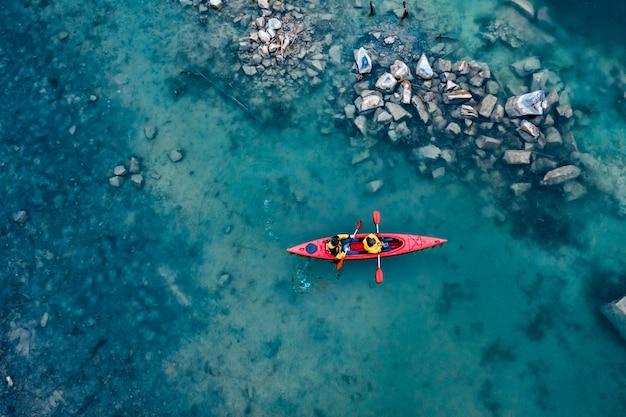 川の赤いボートに浮かぶ2つの運動男