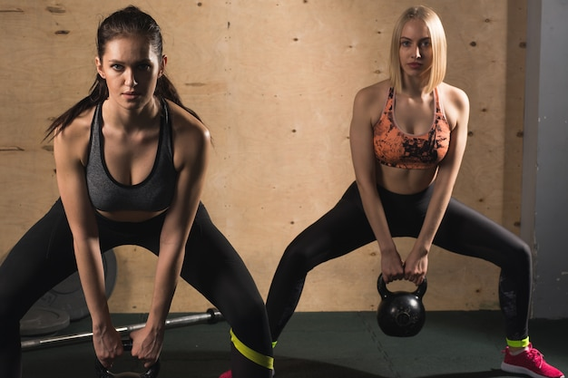 Two athletic womans exercising with kettle bell while being in squat position