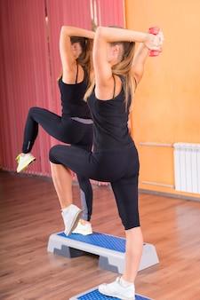 有酸素運動のステップの上で片足でバランスを取りながら、頭の後ろでウェイトを持ち上げる2人の運動女性。