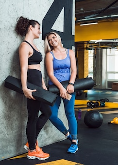 Two athletic women with exercise mat leaning on wall in fitness club