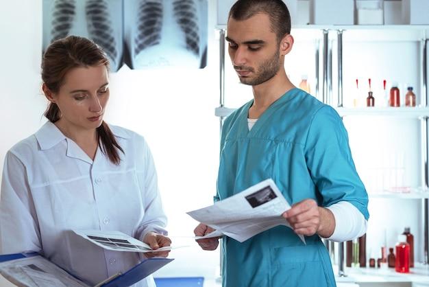 두 명의 세심한 의사 여성과 의료복을 입은 남성이 클립 폴더를 들고 토론