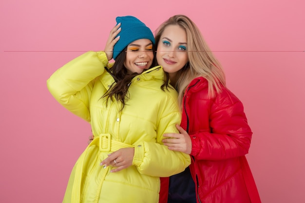 Two attractive active women posing on pink wall in colorful winter down jacket of bright red and yellow color, friends having fun together, warm coat fashion trend, crazy funny faces