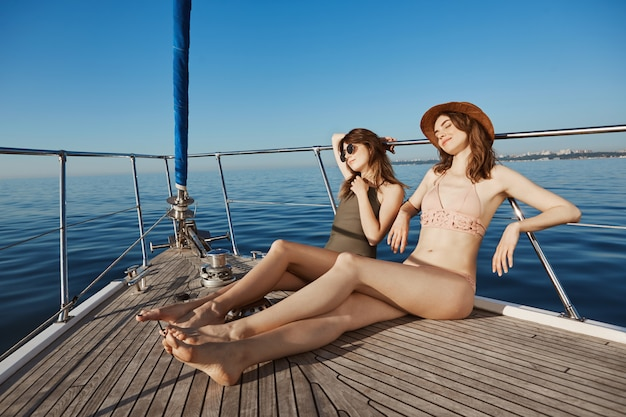 Two attractive adult woman on yacht, sailing in sea and sunbathing on bow of boat, feeling relaxed and pleased. hot women want get tan so they changed in bikinis. summertime happiness