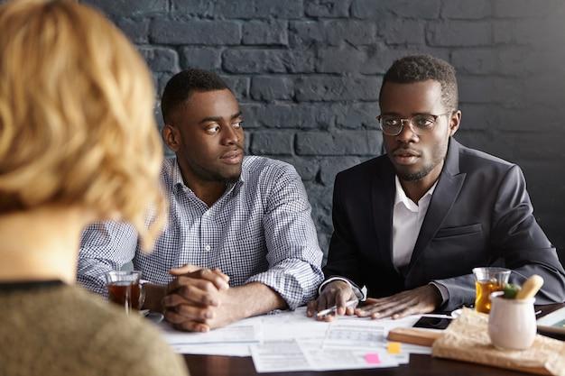 書類をオフィスの机に座ってフォーマルな服装の2人の魅力的なアフリカ系アメリカ人ビジネスマン
