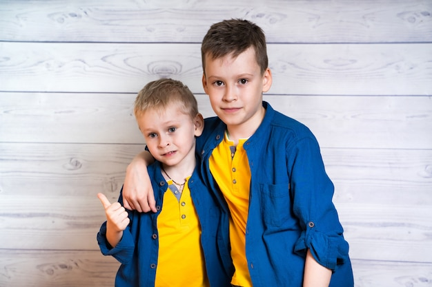 Two attractive boys in blue shirts and yellow t-shirts posing together. portrait of two brothers hugging each other and looking