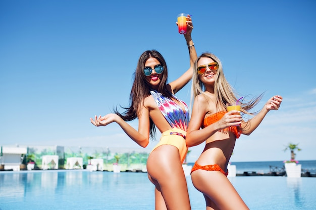 Two attractive brunette and blond girls with long hair are posing near pool on the sun. they wear swimsuit, sunglasses and holding cocktails. they are moving and smiling to the camera.