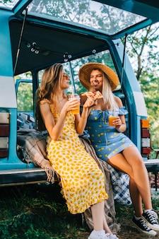 밴 근처에서 레모네이드를 마시고 피자를 먹고, 도로 여행에서 여름 분위기를 즐기는 두 명의 매력적인 쾌활한 여성