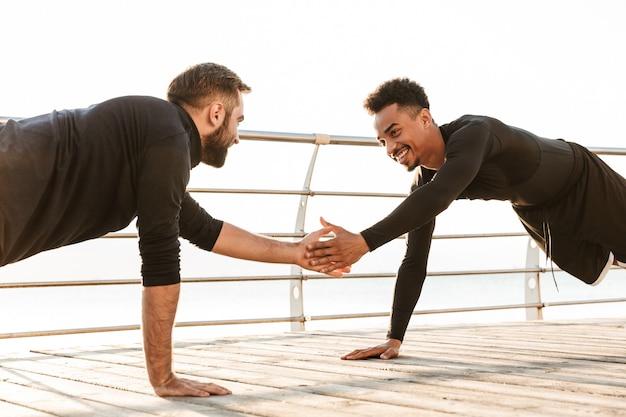 ビーチで屋外で2人の魅力的な自信を持って若い健康なスポーツマン、一緒にトレーニング、腕立て伏せをしています