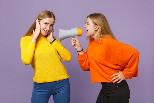 パステルバイオレットブルーの壁に隔離されたメガホンで鮮やかなカラフルな服を着た2人の魅力的なクレイジーな若いブロンドの双子の姉妹の女の子が叫びます。人々の家族のライフスタイルの概念。 。