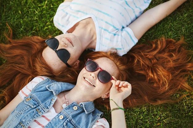 빨간 자연 머리와 빛나는 미소를 가진 두 명의 매력적인 유럽 여자 친구가 잔디에 누워 선글라스와 구름을 응시하는 동안 행복에서 웃고 있습니다. 라이프 스타일과 사람들 개념