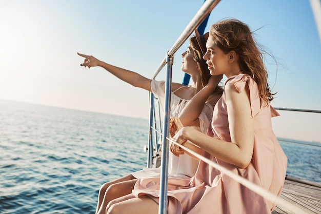 Two attractive european women sitting at bow of yacht, looking at something while pointing at seaside.