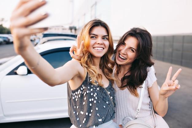 駐車場で楽しい2つの魅力的なファッショナブルな女の子。彼らは自分撮りをして幸せそうに見えます。