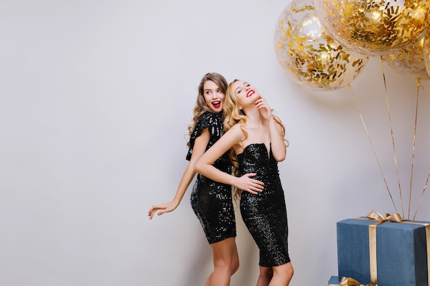 Two attractive fashionable young women in luxury black dresses celebrating party. having fun, elegant look, smiling, true emotions. big present, golden balloons, tinsels.