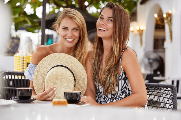 Two attractive female best friends happy to meet together at outdoor cafeteria after spending summer holidays abroad, have pleasant talk with cup of coffee,