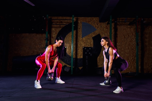 Two attractive fit women athlete performing a kettle-bell swing in gym