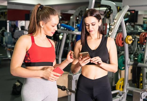 2 привлекательных подходящих женщины в спортзале с умным телефоном