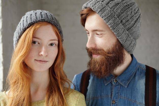 室内で灰色の帽子をかぶった2人の魅力的な友人。長い赤い髪の彼のガールフレンドを愛情と思いやりのある表情で見ているスタイリッシュなひげと幸せなハンサムな男。