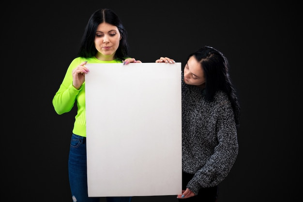 Two attractive funny young women with a white blank poster, isolated on dark background, copy space