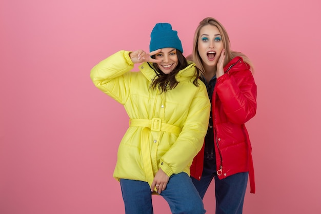 Two attractive girl friends women taking selfie photo on pink wall in colorful winter jacket of bright red and yellow color having fun together, warm coat sportswear fashion trend, crazy funny