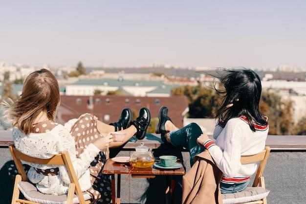 두 매력적인 여자는 도시를 내려다 옥상에 티 파티를 즐길 수