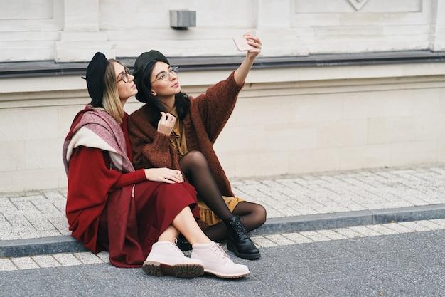함께 앉아있는 동안 셀카를 만드는 두 매력적인 여자, 갈색 머리와 금발. 추운 계절에 어울리는 세련된 의상.