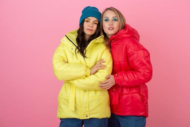 鮮やかな赤と黄色のカラフルな冬のダウンジャケットでピンクの背景にポーズをとる2人の魅力的な女の子
